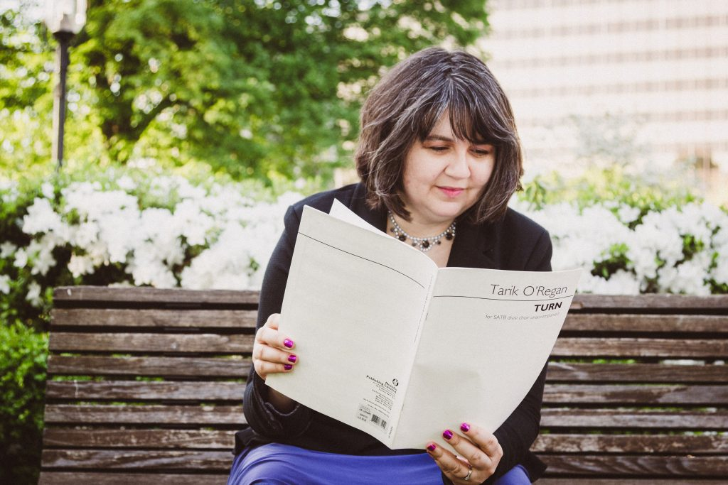 Jamie Klenetsky Fay sits on a bench, reading over a score